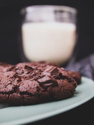 Vegane Schoko-Cookies auf einem Teller vor einem Glas Milch